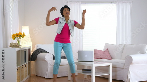 Black woman dancing and having fun in living room