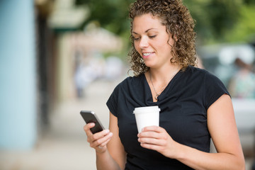 Woman With Coffee Cup Messaging Through Smartphone