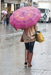 Woman with umbrella walking down street