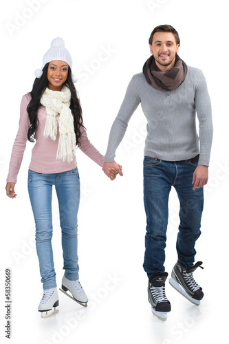 Loving couple skating together holding hands.