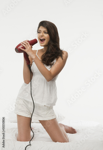 Woman singing into a hair dryer