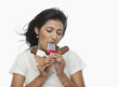 Woman licking one of three ice creams held by her