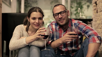 Attractive couple sitting on floor, drinking wine and smiling