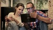 Young couple with tablet computer drinking wine at home