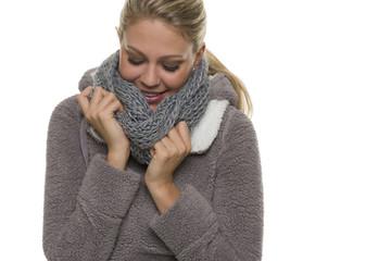 Frau wärmt die Hände im Schal