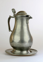 Pewter pitcher on tin plate