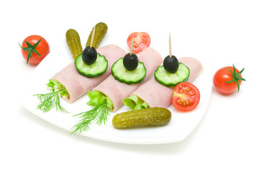 rolls of ham with vegetables on the plate on white background