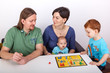 Parents with child and baby in the joint board game