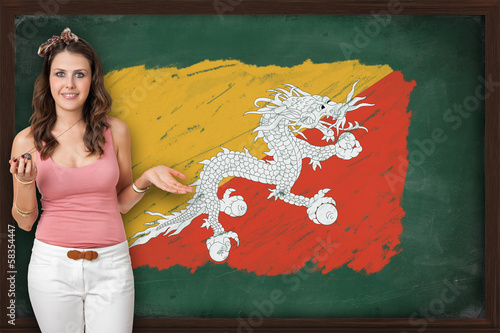 Beautiful and smiling woman showing flag of Bhutan on blackboard