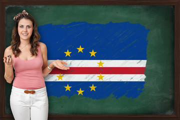 Beautiful and smiling woman showing flag of Cape Verde on blackb