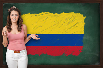 Beautiful and smiling woman showing flag of Colombia on blackboa