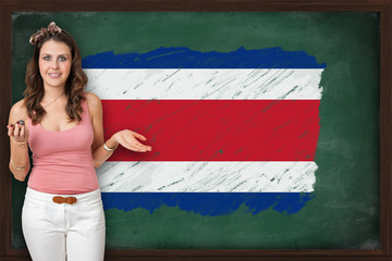 Beautiful and smiling woman showing flag of Costa Rica on blackb