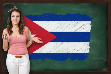 Beautiful and smiling woman showing flag of Cuba on blackboard