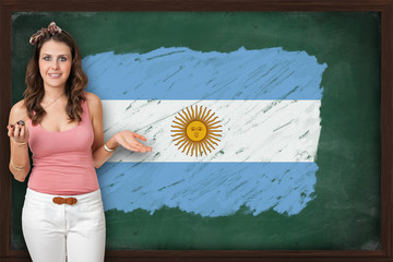 Beautiful and smiling woman showing flag of Argentina on blackbo