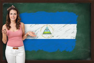 Beautiful and smiling woman showing flag of Nicaragua on blackbo