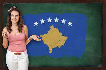 Beautiful and smiling woman showing flag of Kosovo on blackboard