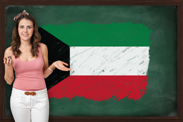 Beautiful and smiling woman showing flag of Kuwait on blackboard