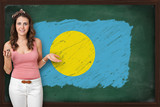 Beautiful and smiling woman showing flag of Palau on blackboard