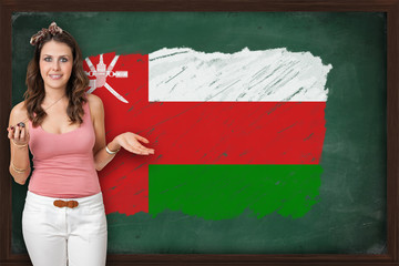 Beautiful and smiling woman showing flag of Oman on blackboard