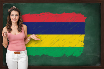 Beautiful and smiling woman showing flag of Mauritius on blackbo