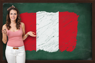 Beautiful and smiling woman showing flag of Peru on blackboard