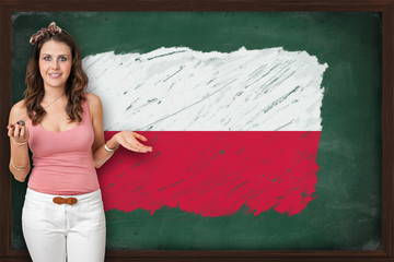 Beautiful and smiling woman showing flag of Poland on blackboard