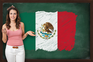 Beautiful and smiling woman showing flag of Mexico on blackboard