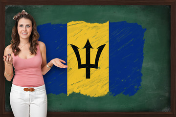 Beautiful and smiling woman showing flag of Barbados on blackboa