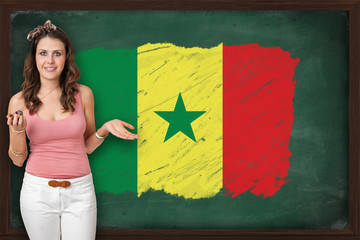 Beautiful and smiling woman showing flag of Senegal on blackboar