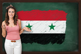 Beautiful and smiling woman showing flag of Syria on blackboard
