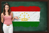 Beautiful and smiling woman showing flag of Tajikistan on blackb