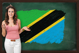 Beautiful and smiling woman showing flag of Tanzania on blackboa