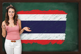Beautiful and smiling woman showing flag of Thailand on blackboa