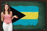 Beautiful and smiling woman showing flag of The Bahamas on black