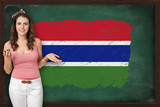 Beautiful and smiling woman showing flag of Gambia on blackboard
