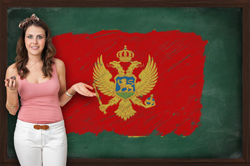 Beautiful and smiling woman showing flag of Montenegro on blackb
