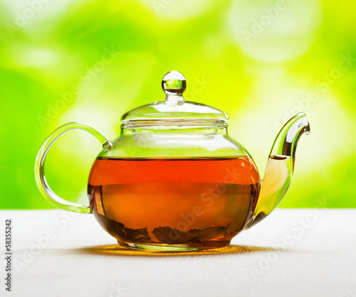 Teapot of fresh tea on natural background