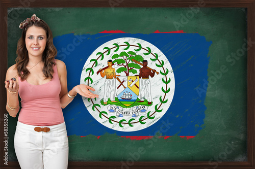 Beautiful and smiling woman showing flag of Belize on blackboard