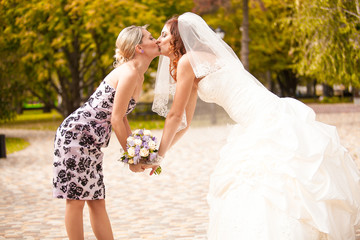 Outdoor portrait of bridesmaid kissing beautiful bride