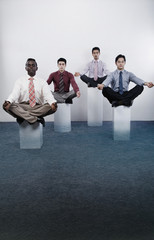Four businessmen practicing yoga