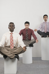 Three businessmen practicing yoga