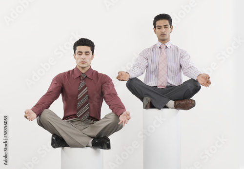 Two businessmen practicing yoga
