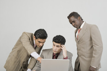 Three businessmen working on a laptop