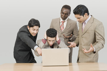 Four businessmen looking shocked in front of a laptop