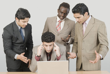 Four businessmen looking stressed in front of a laptop
