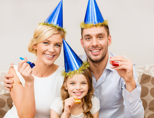 smiling family in blue hats blowing favor horns