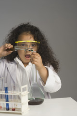 Girl dressed as scientist researching in the laboratory