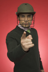 Portrait of a businessman wearing a cricket helmet and pointing