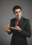 Portrait of a businessman holding a magic lamp