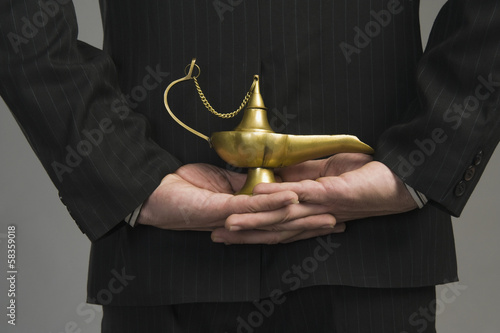 Mid section view of a businessman holding a magic lamp
